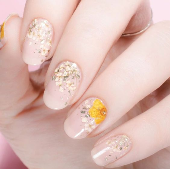 natural nude nails with white and yellow dried flowers painted on