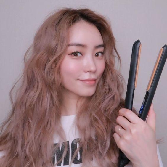 asian girl using a flat iron to create wavy hair