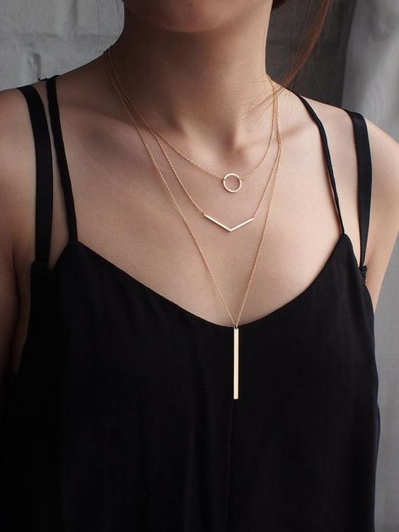 three minimalist necklaces and a black top