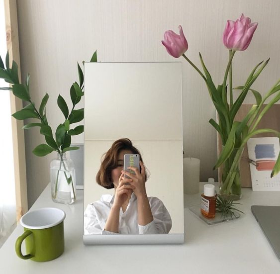 Girl taking selfie using mirror on vanity table with tulips
