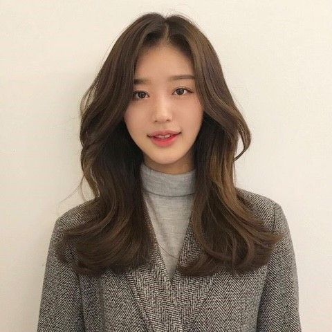asian woman with wavy ash brown hair that ends at the calvicles