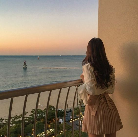 Girl with curly hair looking at the sea