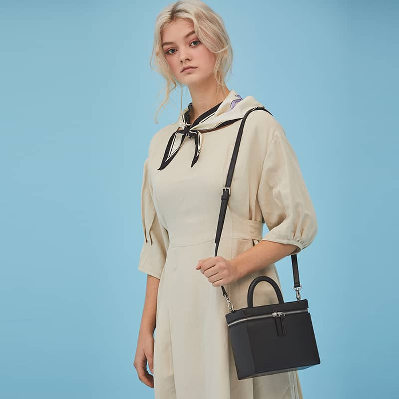 woman wearing a white dress and hold a black ANDSEEYOU Cheese Tote Bag in Ivory over her shoulder