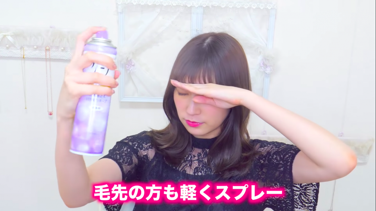 Akari Yoshida applying hairspray and blocking her face
