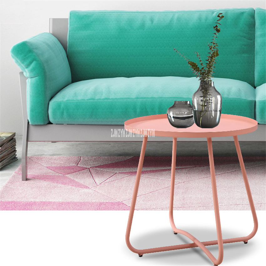 Pink metal side table and green sofa