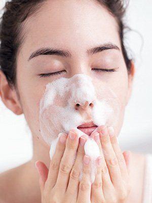 asian woman using foam facial cleanser