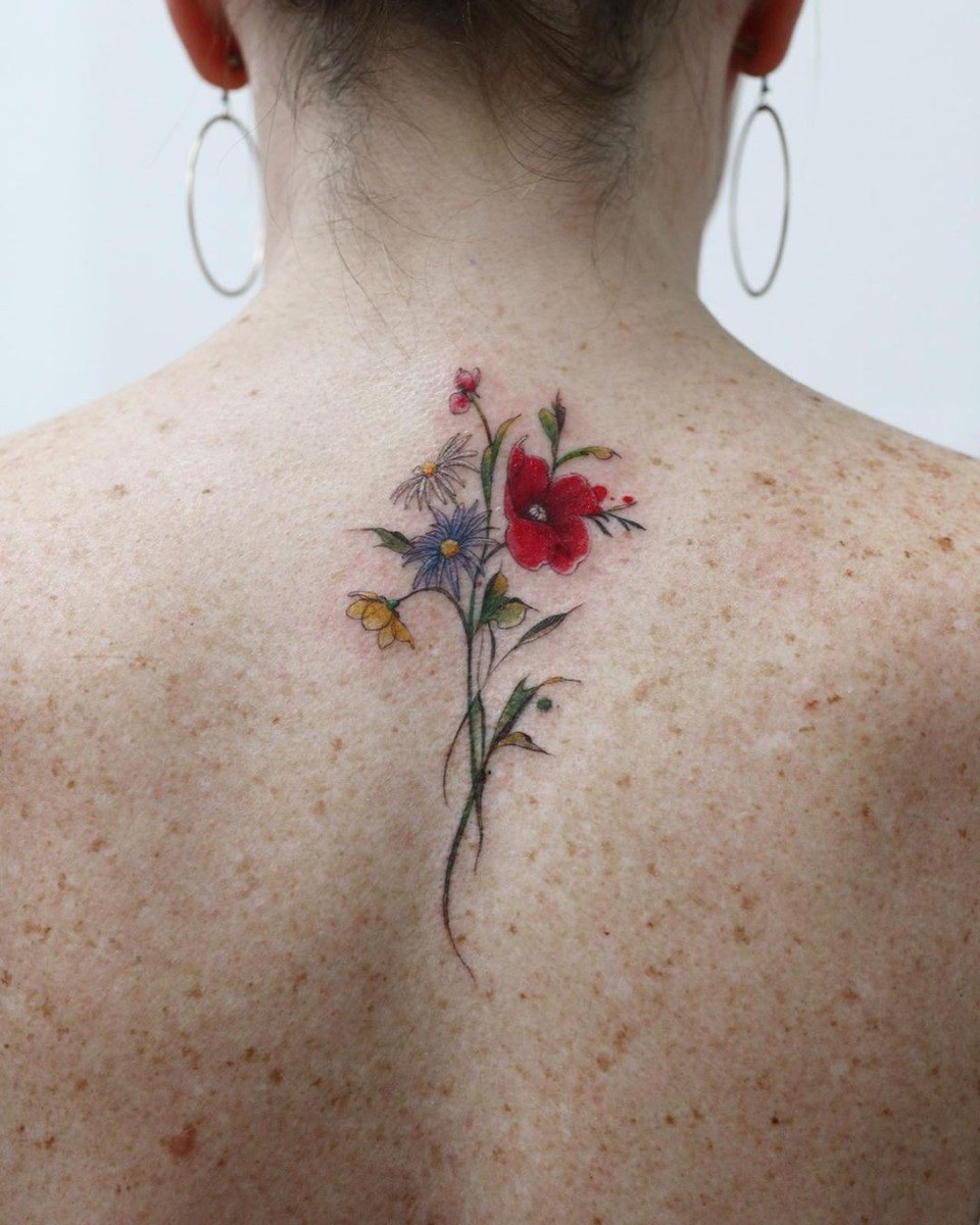 watercolour illustrative floral tattoo on woman's back of neck