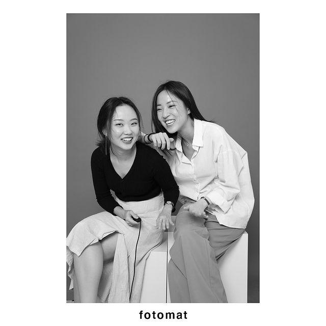 Two girls taking black and white photos at Fotomat Studios