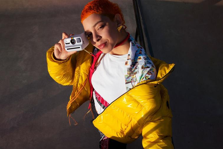 Model holding Polaroid Go