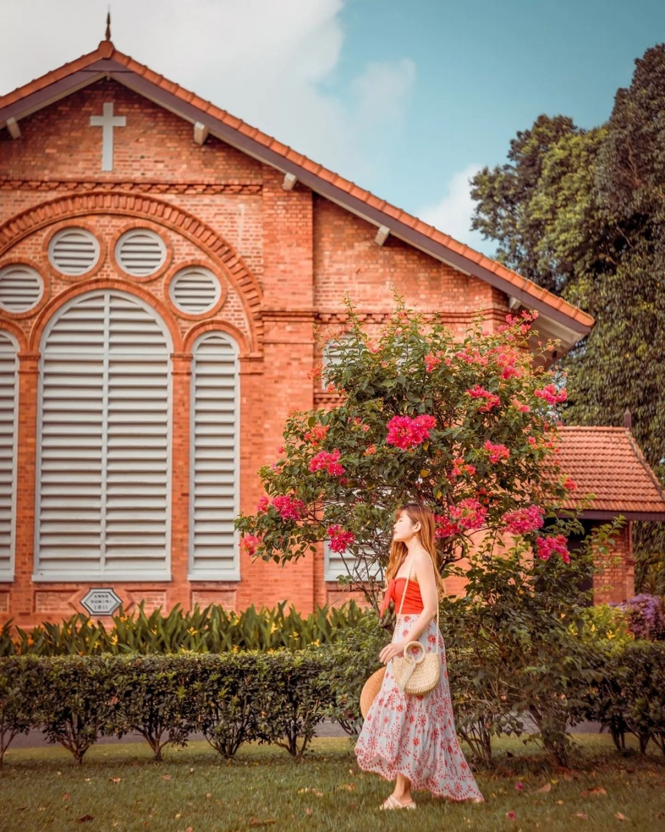 chervon khoo standing in front of flowering tree at saint george church singapore